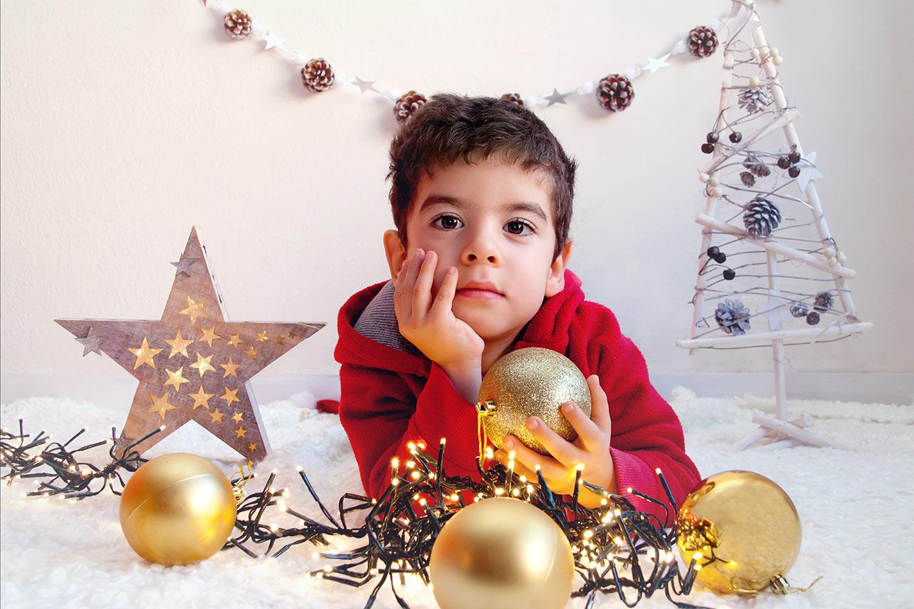 niño con adornos de navidad